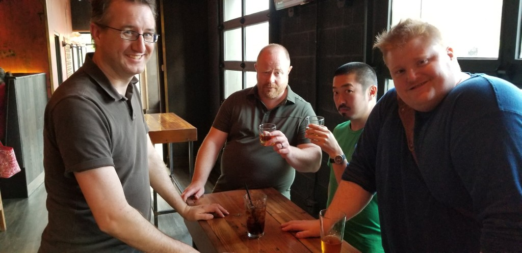 Four people with drinks standing around a table in a bar.
